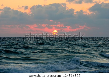 cloudy sunset panorama under the sea waves surface - stock photo