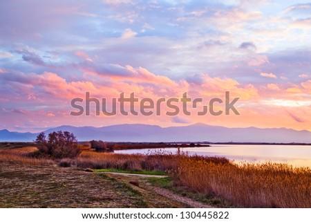 "Cloudy winter sunset at ""Etang de Canet-Saint Nazaire"" lake near Canet plage village, Perpignan city, southern France - stock photo"