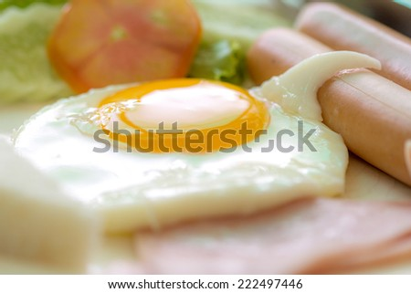 clouse up fried egg in breakfast on the dish - stock photo