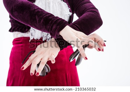 clouse up hands with castanets of a female spanish flamenco dancer in white blouse and vinous flamenco skirt in studio on gray background - stock photo