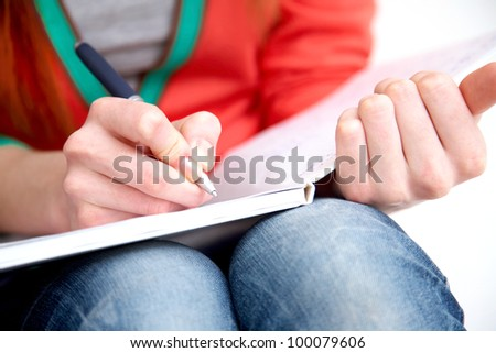 Clouse-up of female hands writing in notebook - stock photo