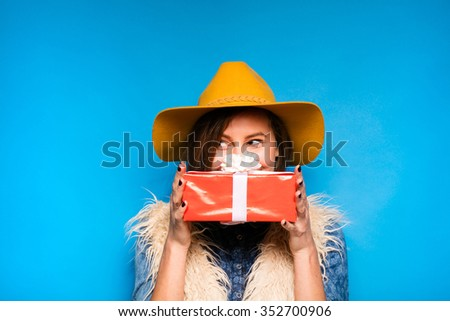 clouseup of young modern woman holding a red gift in hands, on blue background - stock photo