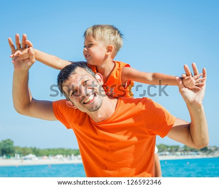 Clouseup portrait of happy father with son laughing and looking at camera on the beach - stock photo