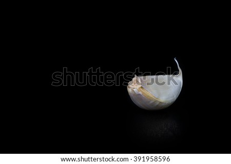 Clove of garlic, isolated black with small DoF. Soft focus. - stock photo
