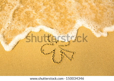 Clover leaf (concept: St. Patrick Day) - written in sand on beach texture,  soft wave of the sea  - stock photo