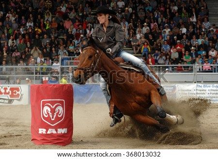 CLOVERDALE, CANADA - MAY 21, 2012: A cowgirl competes in Ladies Barrel Race category at the annual Cloverdale Rodeo on May 21, 2012 in Cloverdale, BC, Canada. - stock photo