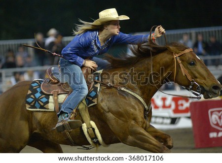 CLOVERDALE, CANADA - MAY 19, 2012: A cowgirl competes in Ladies Barrel Race category at the annual Cloverdale Rodeo on May 19, 2012 in Cloverdale, BC, Canada. - stock photo