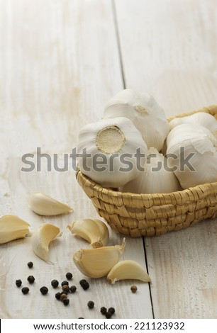 Cloves of garlic in basket on wooden background - stock photo