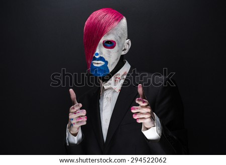Clown and Halloween theme: Scary clown with pink hair in a black jacket on a dark background in the studio - stock photo
