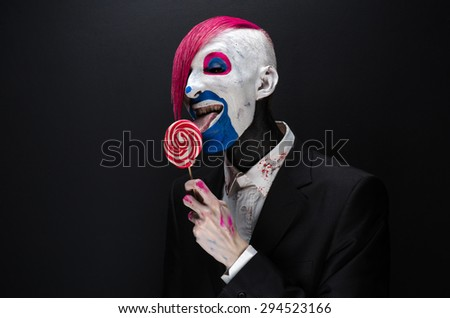 Clown and Halloween theme: Scary clown with pink hair in a black jacket with candy in hand on a dark background in the studio - stock photo