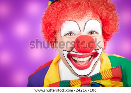 clown closeup with violet background - stock photo