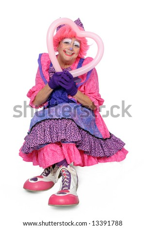 Clown dressed in pink and purple holding a heart - stock photo