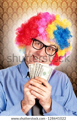 Clown holding american dollars in his hand