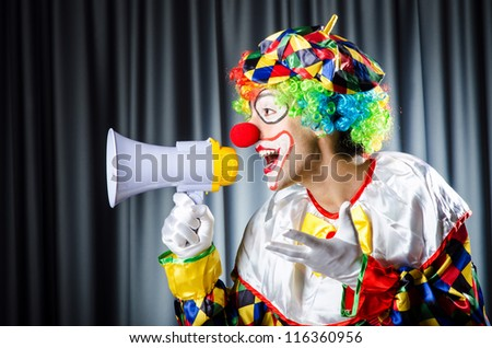 Clown in studio with loudspeaker - stock photo