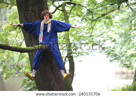 Clown mischiefing on the tree branch, street theater concept - stock photo