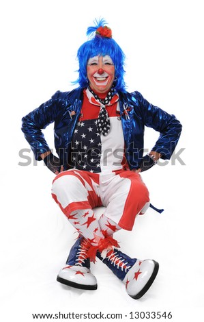 Clown sitting and smiling with hands on hips - stock photo