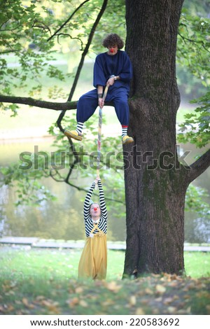 Clown sitting on a tree branch helping other clown to climb up - stock photo