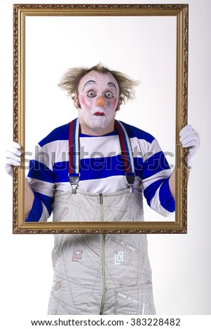 Clown with a frame in his hands - stock photo