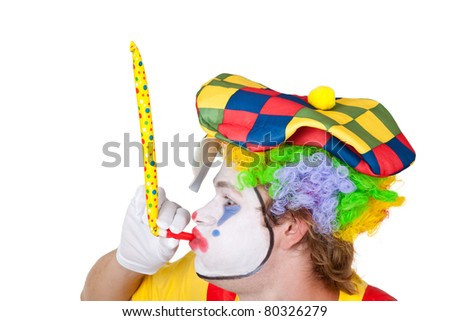 Clown with multicolored cap blowing into a pipe - isolated