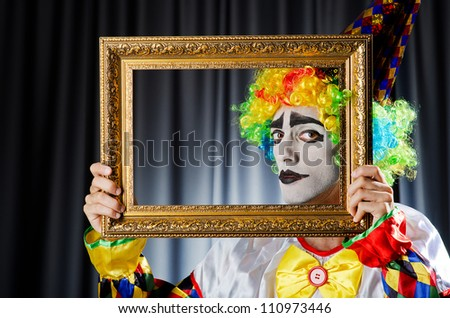 Clown with picture frames in studio - stock photo
