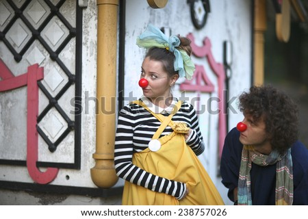 Clowns playing spies, woman and man with red noses and colorful clothing looking out of the corner  - stock photo
