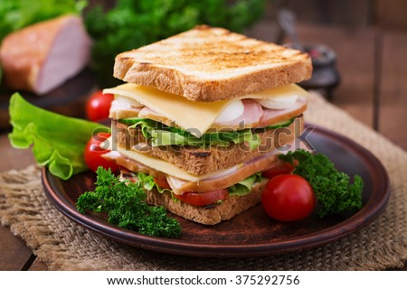 Club sandwich with cheese, cucumber, tomato, ham and eggs.