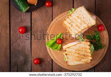 Club sandwich with cheese, cucumber, tomato, ham and eggs. Top view - stock photo