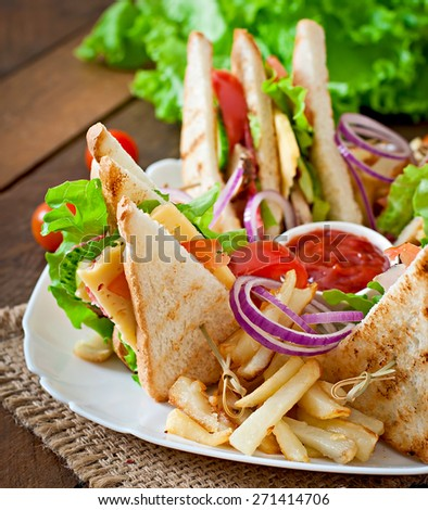 Club sandwich with cheese, cucumber, tomato, smoked meat and salami. Served with French fries. - stock photo