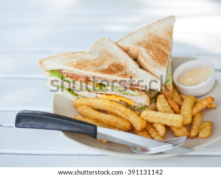 Club sandwich with french fries on a white table. Image with selective focus - stock photo