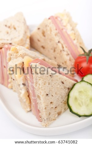 club sandwiches with ham and cheese on a plate close-up