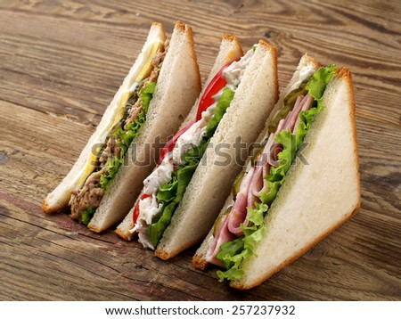 Club sandwiches with tuna, ham and chicken, selective focus - stock photo