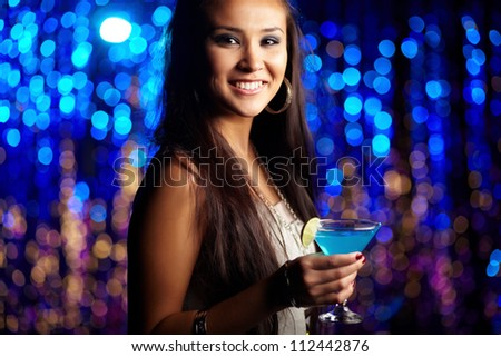 Clubbing girl holding a cocktail and looking at camera with a sensual smile - stock photo