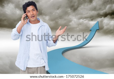Clueless male on his cellphone against blue arrow pointing up against sky - stock photo