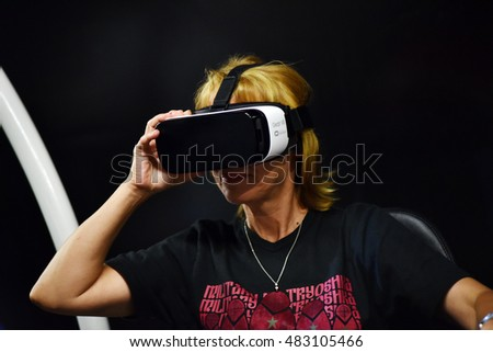 CLUJ-NAPOCA, ROMANIA - AUGUST 6, 2016: Woman tries virtual reality Samsung Gear VR headset and hand controls during the virtual reality exposition, at the Untold Festival