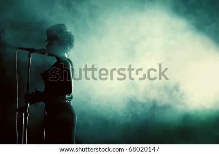 CLUJ NAPOCA, ROMANIA - SEPT. 27: Beate Baumgartner, the female singer of Parov Stelar's band, performs live surrounded by smoke  at Parov Stelar Concert, on September 27, 2009 in Cluj-Napoca, Romania - stock photo