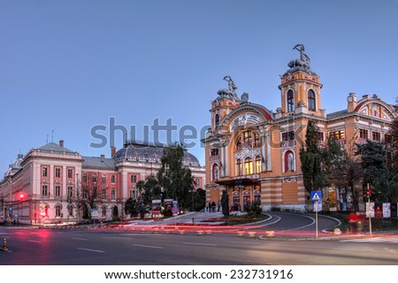 CLUJ, ROMANIA - OCTOBER 18: Twilight in Cluj Napoca, Romania with the Lucian Blaga National Theatre and the Palace of Justice on the evening of October 18, 2014. - stock photo