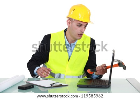 Clumsy architect smashing laptop with hammer - stock photo