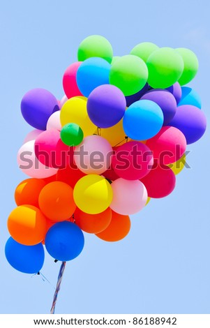 cluster of party balloons against blue sky - stock photo