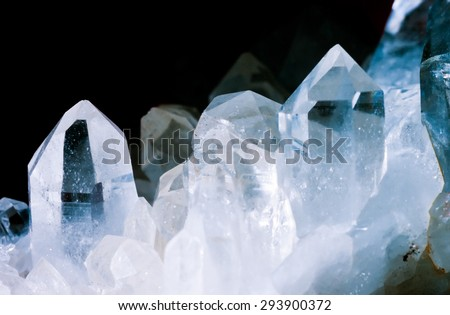 Cluster of rock crystals or pure quartz, a clear macrocrystalline variety of silica (SiO2) isolated on black background. This gemstone is said to have strong healing power. Birthstone for April - stock photo