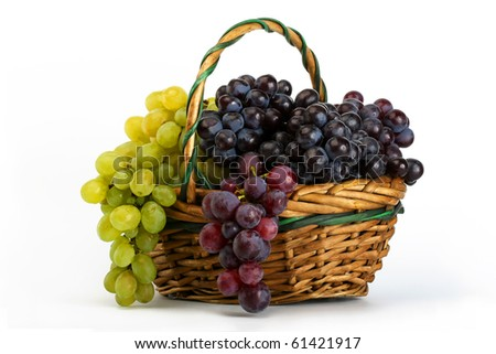 Clusters of yellow and black grapes in a basket on a white background - stock photo