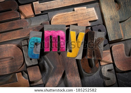 cmyk written with colored vintage letterpress printing blocks on random letters background - stock photo