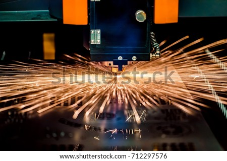 CNC Laser cutting of metal, modern industrial technology. Small depth of field. Warning - authentic shooting in challenging conditions. A little bit grain and maybe blurred.