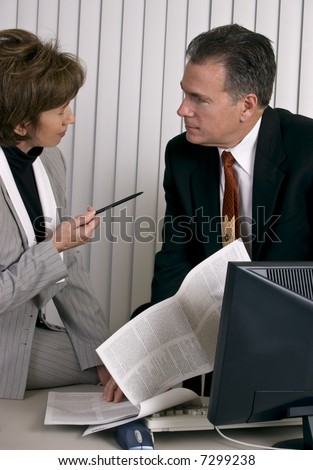 Co-workers engaged in a debate over the contents of a legal document. - stock photo