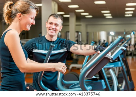 coach and a young girl in the gym exercise - stock photo