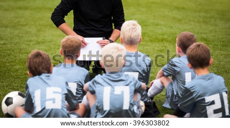 Coach Encouraging Boys Soccer Team. Soccer Football Team with Coach at the Stadium. Coach with Youth Soccer Team. Boys Listen to Coach's Instructions. Coach Giving Team Talk - stock photo