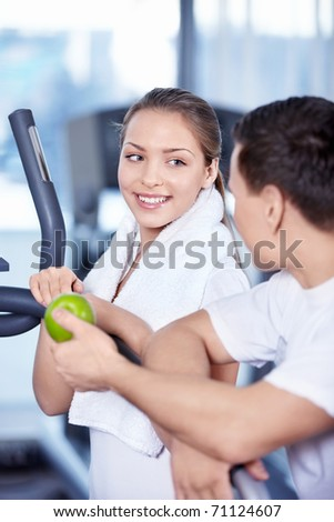 Coach gives young woman a green apple - stock photo