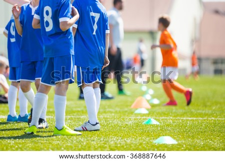 Coach giving children soccer team instructions. Young boys and soccer coach watching football match. Youth reserve players ready to play football tournament - stock photo