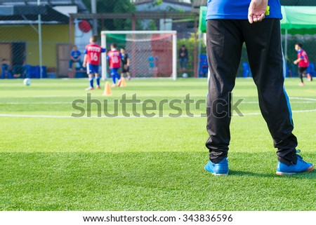 Coach is coaching Children Training In Soccer Team - stock photo