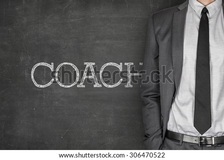 Coach on blackboard with businessman in a suit on side - stock photo