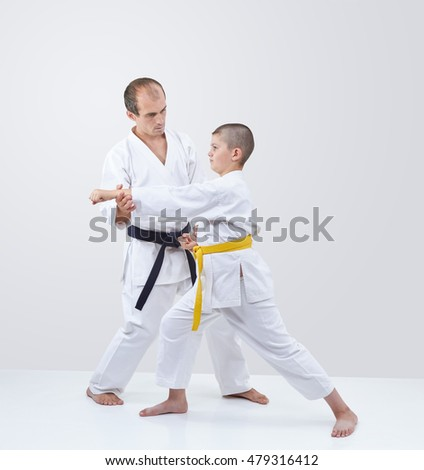 Coach with black belt straightens  karateka boy with yellow belt
